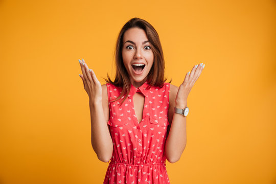 Photo of happy excited amazed young woman in red dress standing with open palms, looking at camera