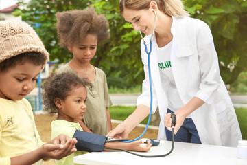 Volunteer doctor measuring blood pressure of poor African child outdoors Fototapete
