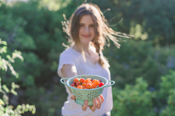 Woman showing bowl with tomatoes