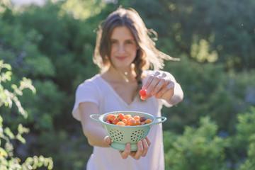Beautiful farmer holding bowl of ripe tomatoes