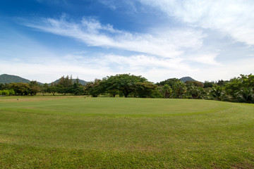 Green grass Golf field in big city park in a sunny day with blue sky and clouds for background.