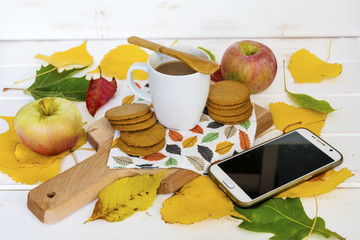 coffee ,apples and autumn leaves with mobile phone.Autumn concept