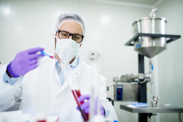 Close up of a scientist with face mask and gloves working with red liquid in a tube.