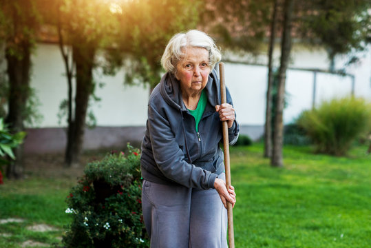 Pretty senior woman holding rake in the house backyard.
