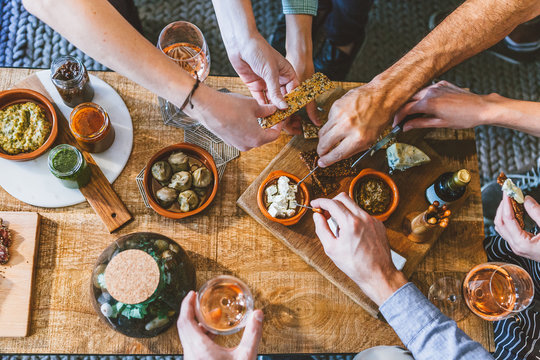 hands picking food on an upholstered table for a party