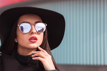 Street portrait of attractive model in trendy sunglasses and stylish hat. Female fashion concept