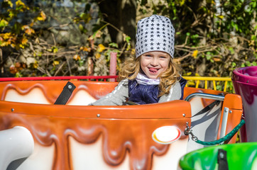 A small charming girl goes for a drive in an amusement park on a merry-go-round, in a large coffee mug, on a sunny autumn day
