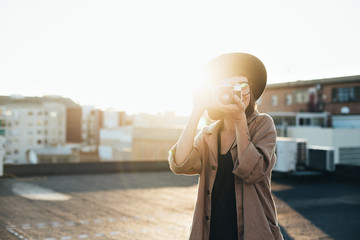 Smiling and laughing young woman, professional photographer stands on top of rooftop in city on warm summer evening, makes photos with retro vintage analog camera