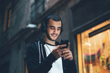 Handsome young man in black hoodie wears big wireless music headphones and changes audio tracks on smartphone, he smiles when looks at phone screen