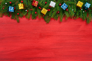 Red Christmas background. Christmas fir tree with decorative gifts on red wooden background, copy space.