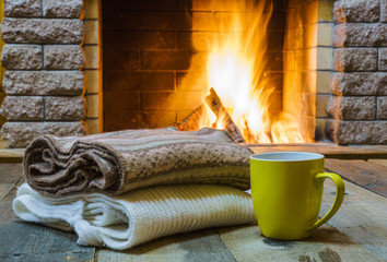 Mug  for tea or coffee,  woolen things near  cozy fireplace, in country house, winter vacation, horizontal.