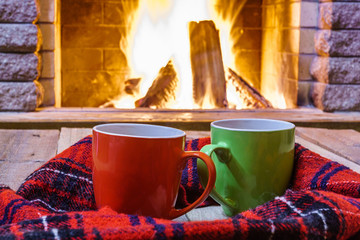 Two  mugs  for tea or coffee,  woolen things near  cozy fireplace, in country house, winter vacation, horizontal.