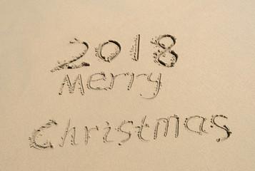 2018 Merry Christmas handwritten in sand on beach