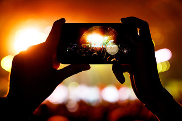 Fan taking photo of concert at festival by smatphone
