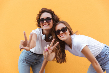 Two happy cheerful teenage girls in sunglasses showing peace gesture