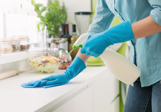 Woman cleaning with a spray detergent