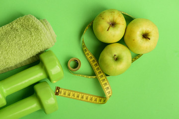 Dumbbells in bright green color, twisted measure tape, towel, fruit