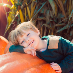 adorable toddler boy laying on pumpkin during fall autumn season