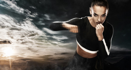 A strong athletic, woman boxer, boxing at training on the sky background. Sport boxing Concept with copy space.