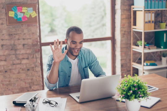 Hey there! Young cheerful afro american guy is waving in camera while having video call sitting at his work station in casual clothes at home