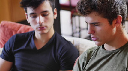 Two young male friends talking and chatting while sitting on sofa at home, relaxing with serious expression