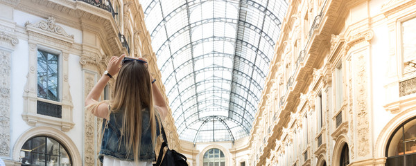 Pretty tourist teenager taking a photo with her mobile phone in the Vittorio Emanuele shopping arcade in Milan, Italy