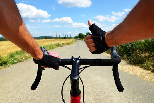 Hands in gloves holding handlebar. Cyclist rides on a road bike.