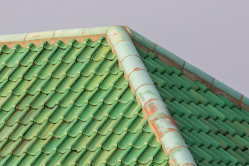Green colored curved clay roof tiles with ridge corner.