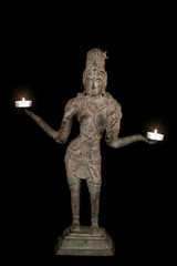 Hinduism and spiritual enlightenment with goddess Lakshmi holding burning candles with starburst lens flare