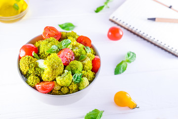 Top view Salad Bowl with cherry tomatoes, and broccoli and diet notebook on the white wooden background. Healthy lifestyle concept. Detox, diet, vegitarian. Selective focus. Text space.
