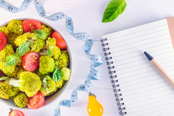 Top view Salad Bowl with cherry tomatoes, broccoli, measuring tape and diet book on the white wooden background. Healthy lifestyle concept. Detox, diet, vegitarian. Selective focus. Text space.