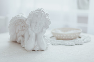 Macro photography of white porcelain figurine of angel lying on table.