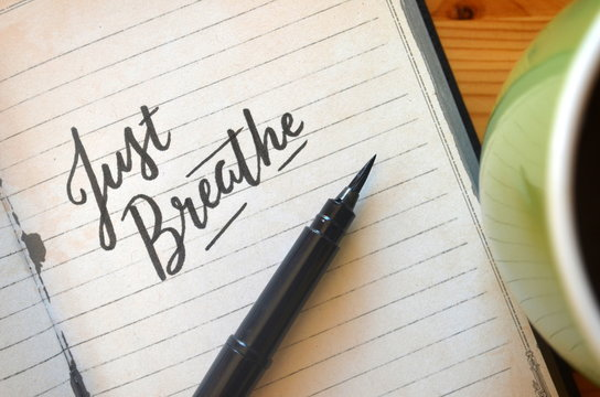 JUST BREATHE brush calligraphy in notebook with cup of coffee on desk
