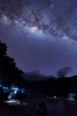 Milky Way landscape. Clearly Milky way above Lake Segara Anak inside crater of Rinjani mountain on night sky. Lombok island, Indonesia.