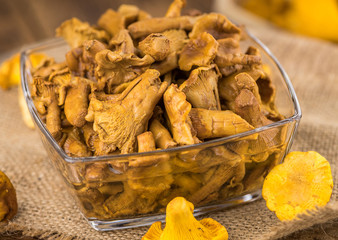 Portion of Preserved chanterelles on wooden background, selective focus