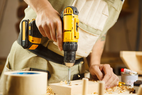 Wood boring drill in hand drilling hole in wooden bar