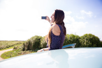 Young woman takes a selfie from a car