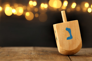 Image of jewish holiday Hanukkah with wooden dreidel (spinning top) and gold lights on the table.