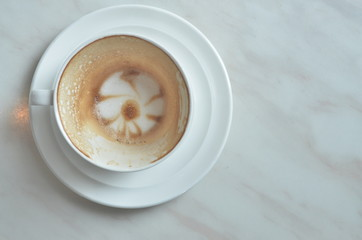Cup cappuccino is Finished drink(with a flower pattern on the surface) on White marble table.