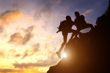 Asia couple hiking help each other silhouette in mountains with sunlight. Wall mural