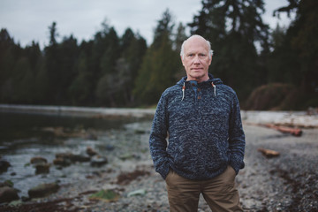 Portrait of senior man standing on beach outside looking at camera