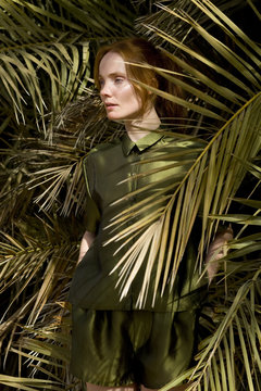 young woman in green clothes among palm leaves