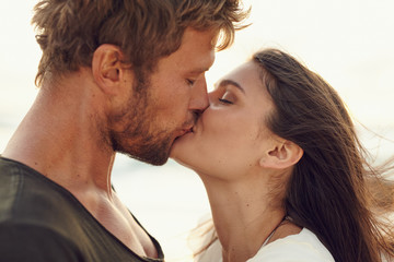 Closeup portrait of romantic young couple kissing at the beach