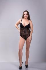 Young beautiful plus size model in shapewear, xxl woman in slimming underwear on gray studio background