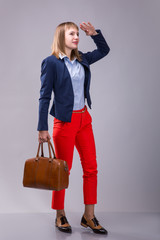 girl in red pants with a leather bag looking into the distance