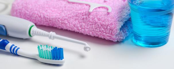 Dental hygiene. Toothbrush, mouthwash, pink towel, dental floss, oral irrigator. Horizontal photo.