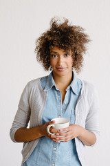 A women stands holding a cup of coffee while looking at the camera.