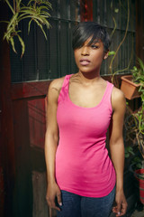 Dark skinned model in pink top stands in front of a wooden door