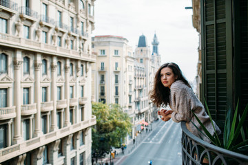 Woman looking at the city from her balcony