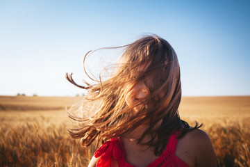 Portrait of a little girl in a wheat field on a windy summer day